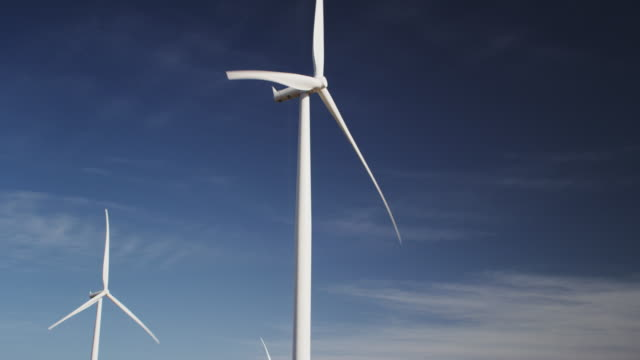 Clean energy, electrical generating wind turbines agains a beautiful blue sky.