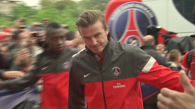 Exterior shots David Beckham PSG team members enter Paris Saint Germain stadium Parc des Princes on red carpet past crowds of fans mascot David...
