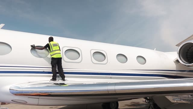 Cleaners polish the fuselage and engine nacelle of a Gulfstream business jet manufactured by Aerospace Corp during preparations ahead of the 51st...
