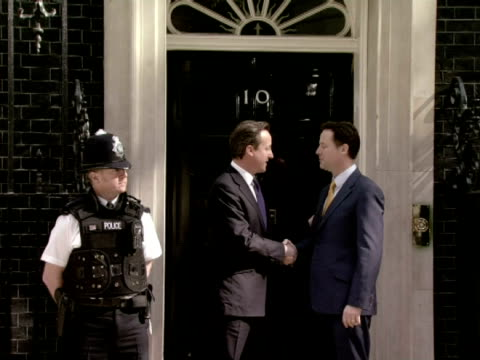 exterior shots Nick Clegg arrives at Downing street is greeted on the doorstep of Number 10 by David Cameron where both men chat wave to the press...
