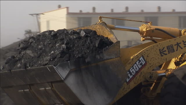 Exterior shows workers and vehicles at coal mining operation