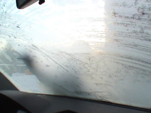 cleaning a car window in early morning