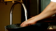 Cleaning hands under faucet