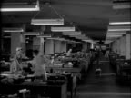 MS of cleaning ladies at work in spacious office / HA of two women sweeping ticker tape and paper in Montreal Stock Exchange Women cleaning office on...