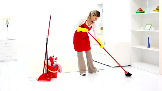 Cleaning lady tidying up a room.