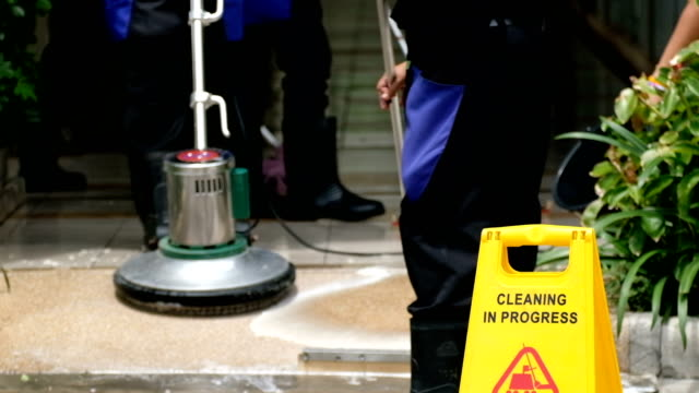 Cleaning service team cleaning floor with Scrubber machine and cleaning in process label