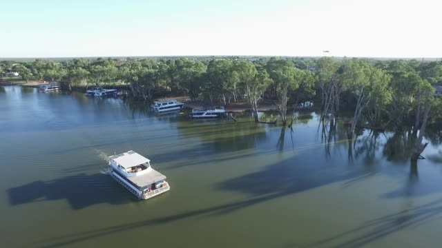 Clear sky Drone aerial over Murray River Mildura houseboat cruises along past other houseboats moored along river bank reflection of sun on river pan...