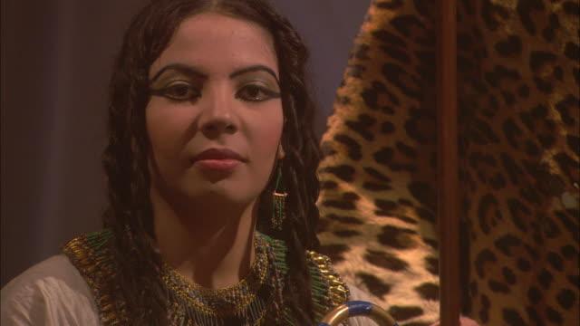 Cleopatra sits near a man wearing a cheetah print robe.