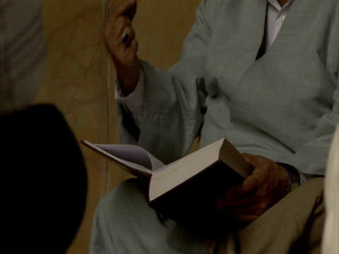 Cleric holding Koran, gesticulating with hands, Iran (sound available)
