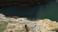 WS HA Cliff diver leaping off cliff into ocean / Acapulco, Guerrero, Mexico