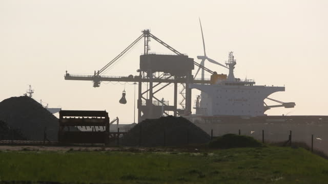 Climate change heaven and hell, cranes unloading coal by the Tata steel works in Ijmuiden, Netherlands, at sunset with a wind turbine producing renewable energy.