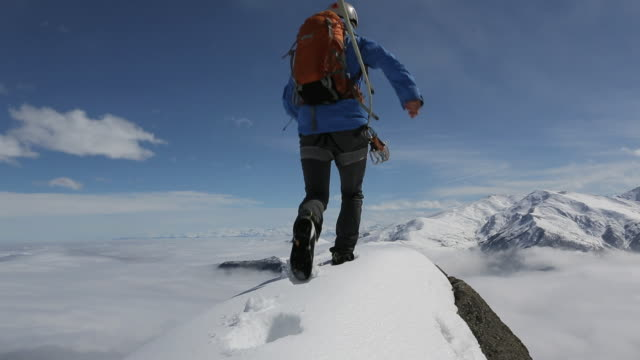 Climber approaches snowy mtn summit, arms outstretched