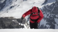 Climber arrives at a snow-covered mountain peak