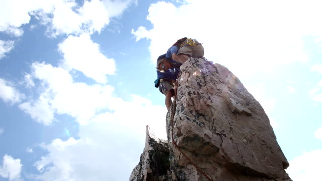 Climber ascends vertical pinnacle above mountains