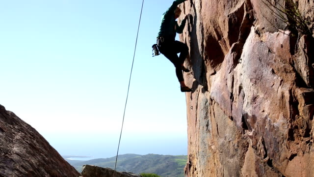 Climber belays teammate on steep cliff above sea