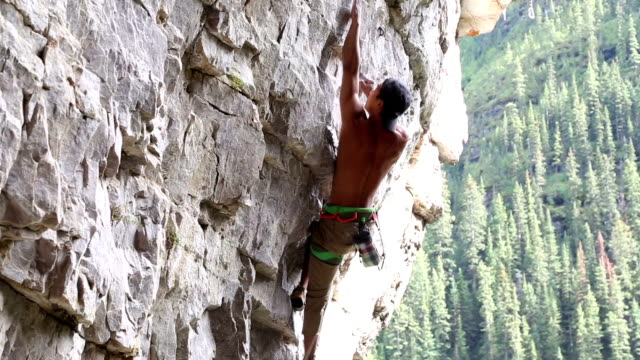 Climber belays teammate on steep cliff above valley