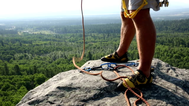 Climber prepares rope/ gear for rappel (abseil)
