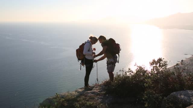 Climber teaches woman climbing knots above sea
