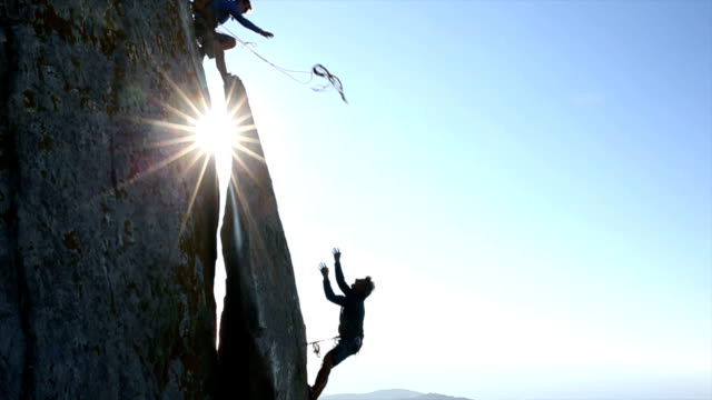 Climber throws rope to teammate, on cliff above hills, sea