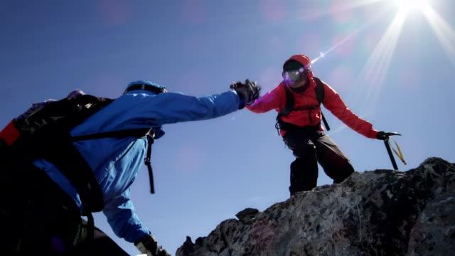 Kletterer helfen einander über Felsen auf die Berge