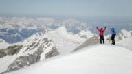 Climber exultant su un picco di montagna coperta di neve