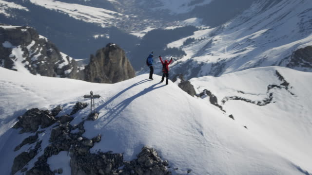 Climbers exultant on a snow-covered mountain peak with a cross on it