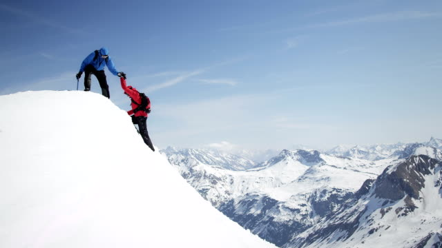 Climbers helping each other arrive at the snow-covered mountain peak