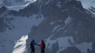 Climbers shaking hands on a snow-covered mountain peak