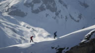 Climbers walk on a snow-covered mountain