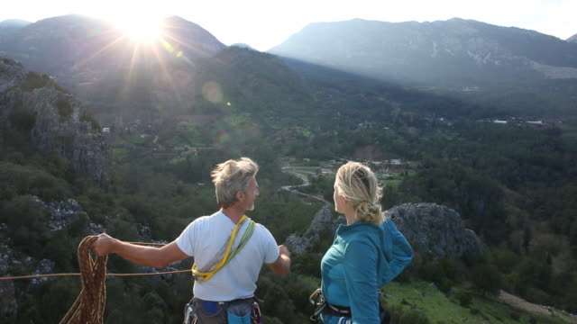 Climbing couple look off from summit, coil rope