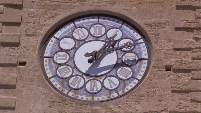 A clock hand turns over a stained-glass surface.