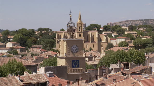 A clock tower and church rise above the tile rooftops of - Darty salon de provence ...