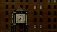 A clock tower stands in front of an office building in Detroit. Available in HD.