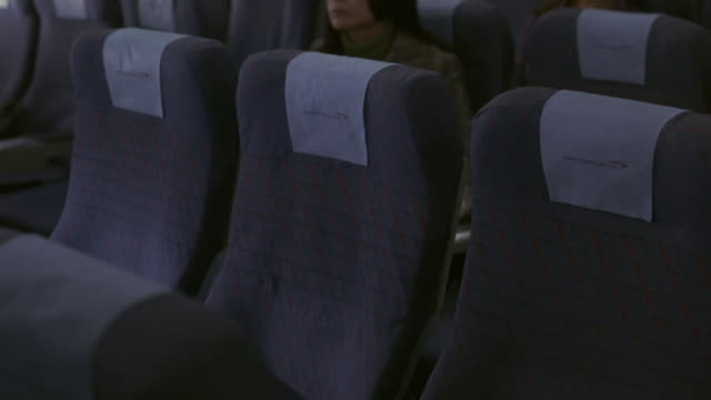close angle of empty center row of seats in airplane. passengers, traveling men and women file down aisles and take their seats leaving center seats vacant. flying.
