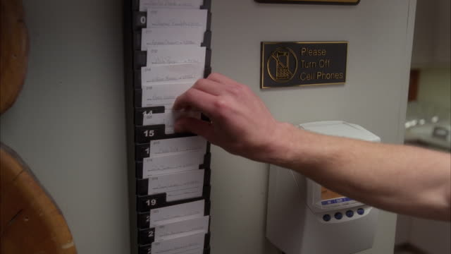 close angle of man's hand placing time card into time stamp machine in office. could be break room. sign reads please turn off cell phones.