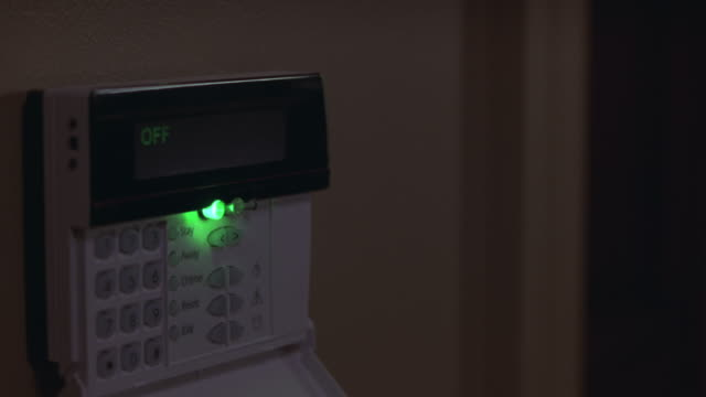 Close angle on alarm panel next to doorway with green light and status message of off. zoom in.