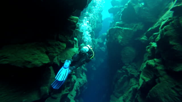 Close in view of a scuba diver swimming through the narrow section of the Silfra Fissure in Thingvellir National Park Iceland.