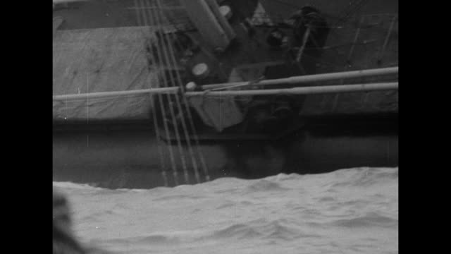 Close shot from British tugboat of badly listing cargo ship SS Flying Enterprise / shot on board tugboat of rough sea / shot from tugboat of cargo...