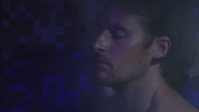 Close shot, man into a steam sauna