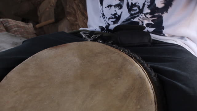 Close shot of a man playing a djembe drum.