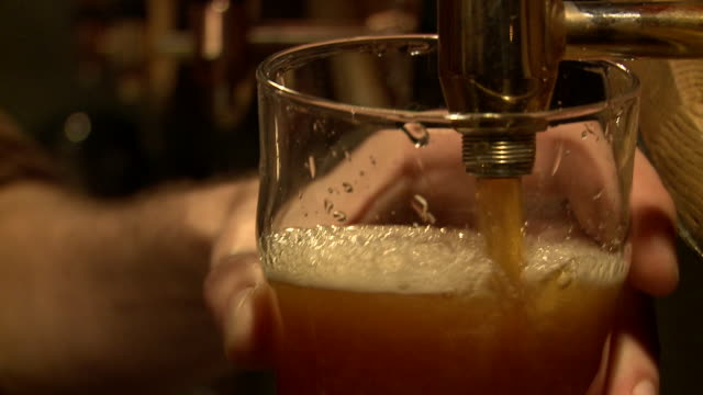 Close shot of a man pulling a pint of beer in a pub.
