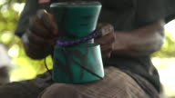 Close shot of a man tying colourful cords around a djembe drum.