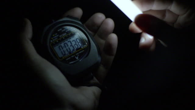 Close shot of a person using a digital stopwatch.