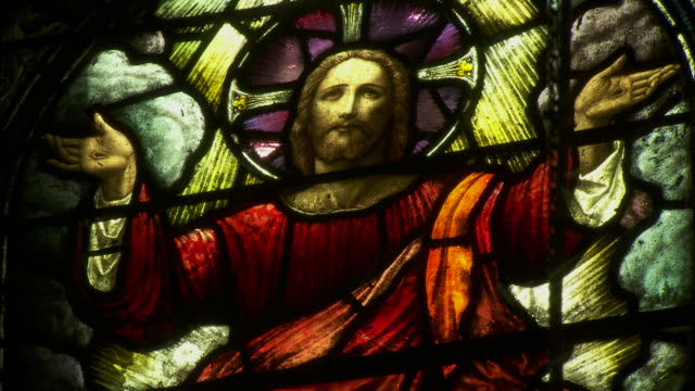Close shot of a stained glass windown, depicting an image of Jesus Christ.