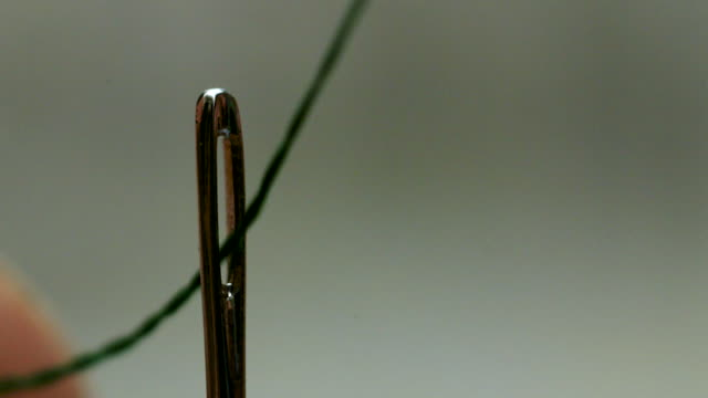 Close shot of a thread being pushed through a needle.