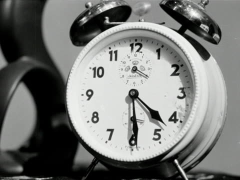 Close shot of a white alarm clock with two large bells on top ringing
