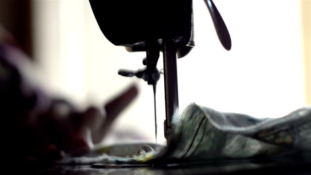 Close shot of sewing machine and moving cloth.