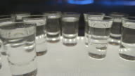 Close shot of shot glasses being taken from a tray.
