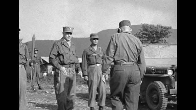 Close side view of line of soldiers standing at attention / general standing at microphone speaking then turning away / CU officer reading medal...