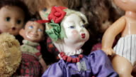 Close tracking shot across a variety of old dolls.